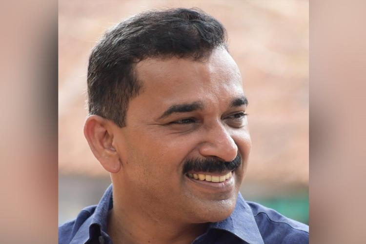 Kerala CPIM leader P Biju in a blue shirt smiling and looking to his left