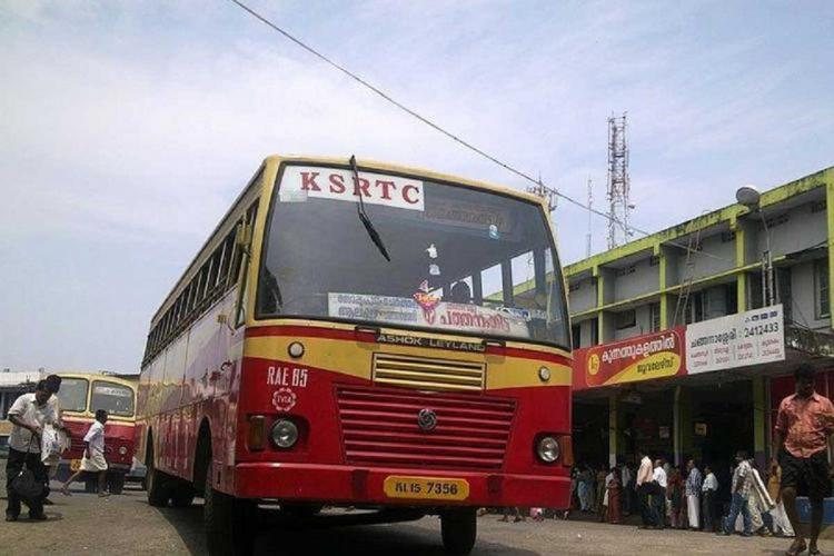 A Kerala RTC bus at a stand with people standing around and another bus behind it