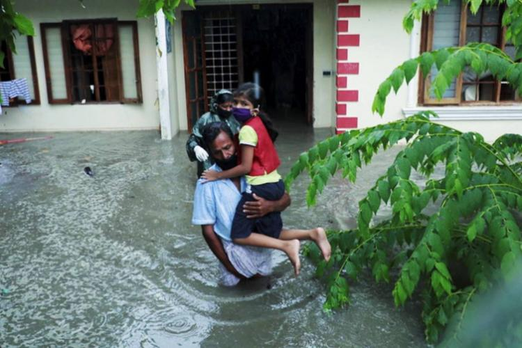 Man carrying daughter out of a flooded house in Kochi
