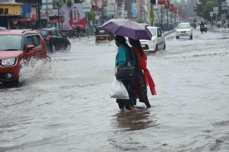 Two women holding an umbrella crossing a road which is inundated after rains