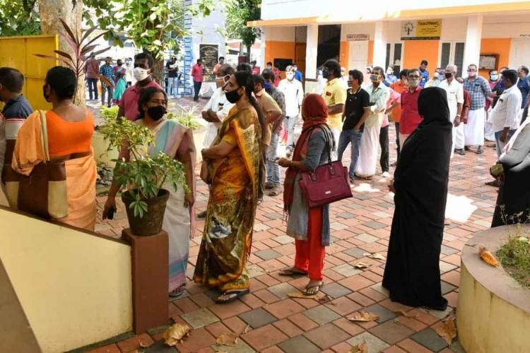 Women and men standing in front of polling booth in Kerala