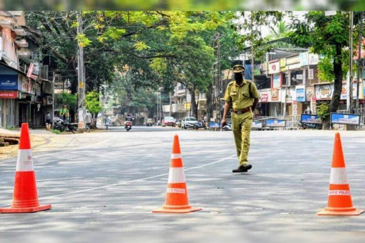 A policeman walks through a deserted road in Kerala where orange and white road cones are placed