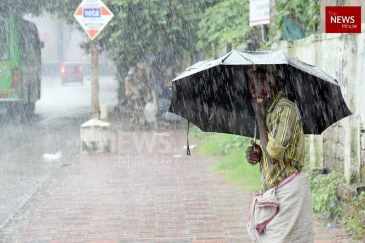 A man wearing shirt and mundu stands under an umbrella by the side of a street in heavy rain