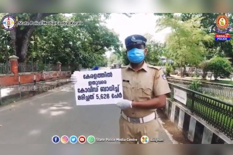 A police official stands at the side of an empty road lined by trees with a placard carrying a Malayalam message on the number of Covid-19 cases