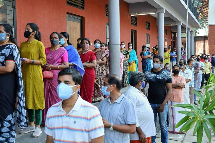 Two lines of voters in a Kerala election one row is of women and the other of men