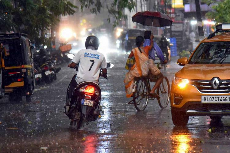 A man in a two wheeler passes by a car during a rainy day A man going in cycle in front of him carries a woman on the back seat who is holding an umbrella up