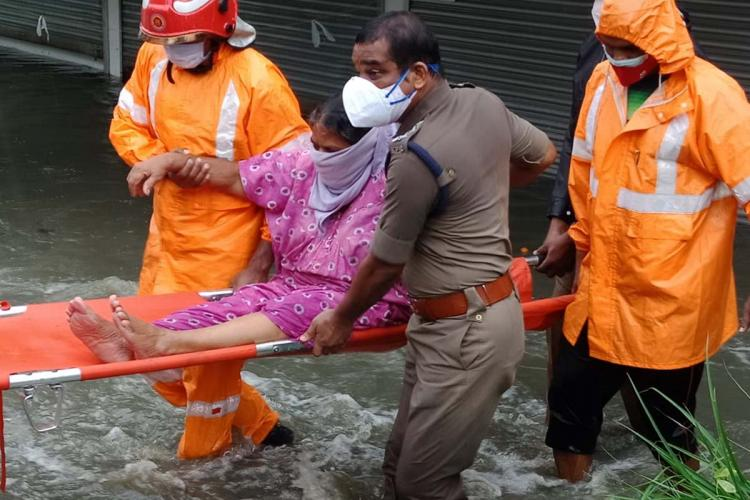 Kerala police and rescue team helping a woman when water inundated in rains