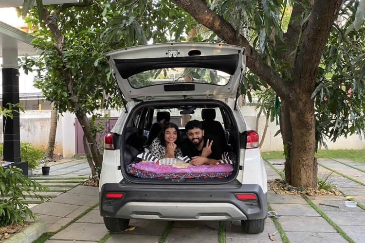 Kerala travel vlogger couple Lakshmi and Harikrishnan pose from the bed set up in their car by folding the back seat The car is parked in the shady courtyard of a house