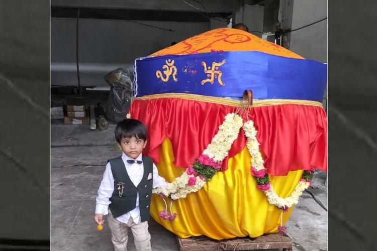 Khairatabad Ganesh Laddu weighing 1100kgs is placed and a boy standing beside the laddu