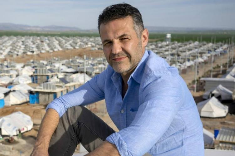 Author Khaled Hosseini in a blue shirt with his arm on his folded knee with many small white buildings in the background
