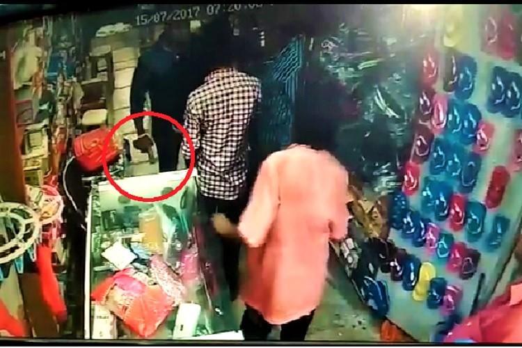 Watch Two Telangana cops assault shopkeeper in Khammam threaten him with gun