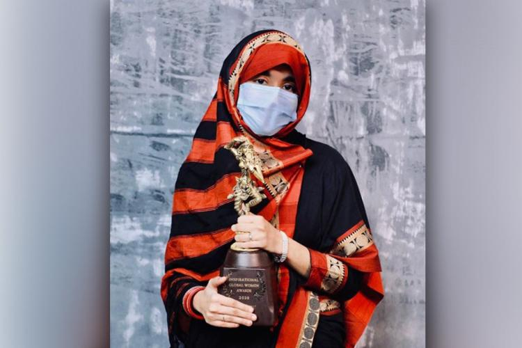 Khatija Rahman wearing a black and red saree and holding an award