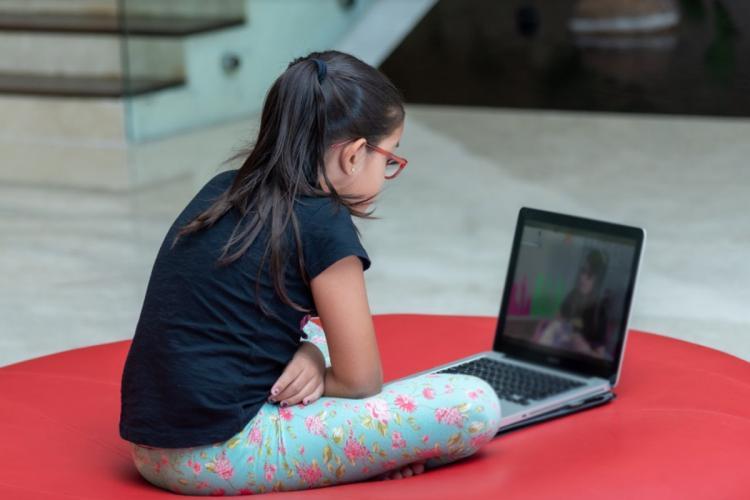 A girl watching a cartoon show on laptop