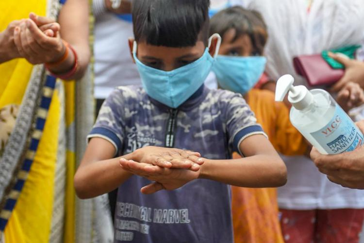 A small boy in mask sanitising his hands