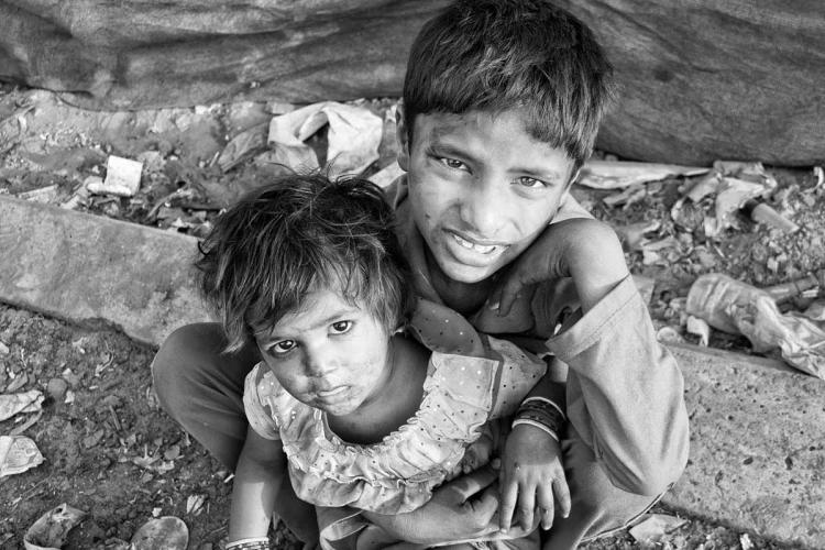 Photo of children near a street engaged in begging