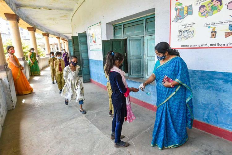 Female teacher giving hand sanitiser to a girl student at school