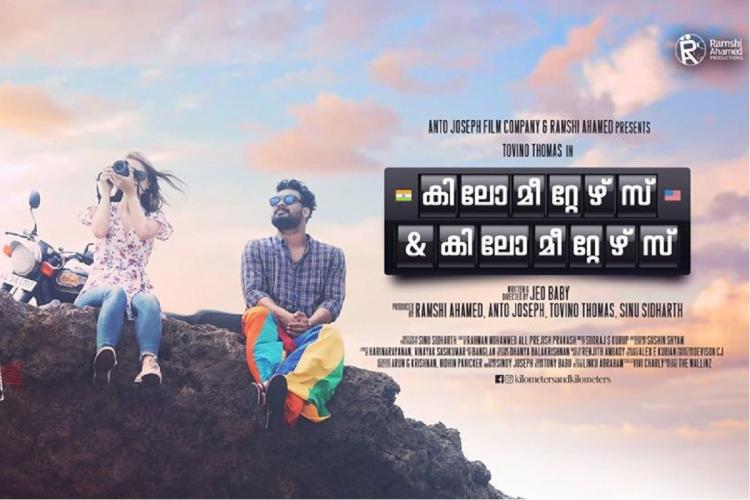 A white woman and actor Tovino Thomas sit on rocks against a rainbow sky with a bike parked behind them It is a poster of a film whose name and details are on the right side