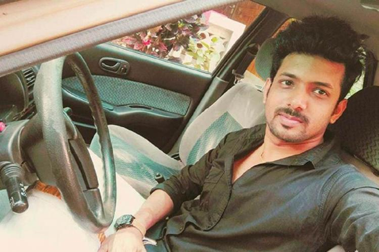 Kiran wearing a black shirt is inside a car, sitting before the steering and the photo is a selfie