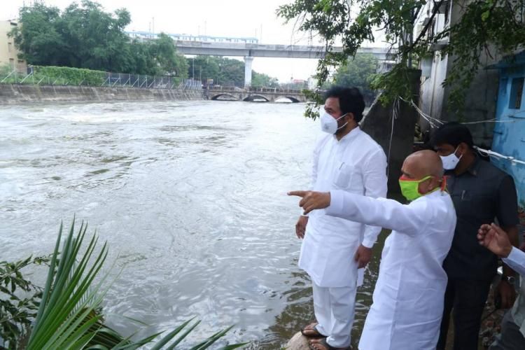 MoS Kishan Reddy visiting inundated areas in Hyderabad he is wearing white clothes and wearing a mask an official next to him is pointed at a stream while talking to him