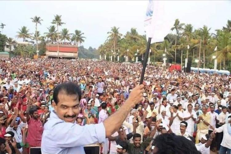 Twenty20 head Sabu Jacob waving party flag standing in the middle of workers.