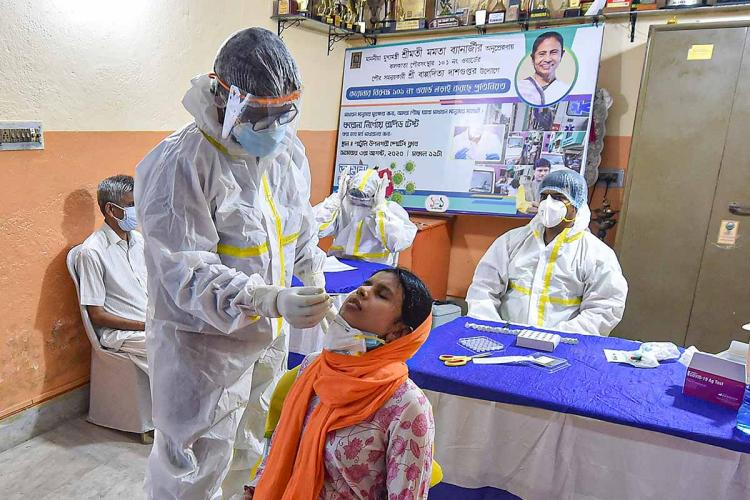 A health worker in a PPE suit collecting nasal swab saple from a woman for coronavirus test