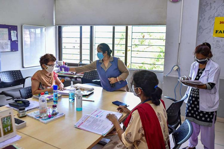 Staff in a school having their temperature scanned by a worker in Kolkata the staff are seated at a table in a staff room