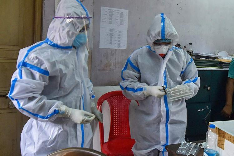 the picture shows two healthworkers wearing personal protective equipment looking at a testing kit and trying to open it the workers are indoors and red plastic chairs are seen behind them
