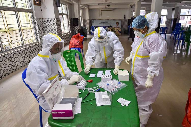 Frontline workers during the coronavirus pandemic wearing full PPE kits huddled around a table