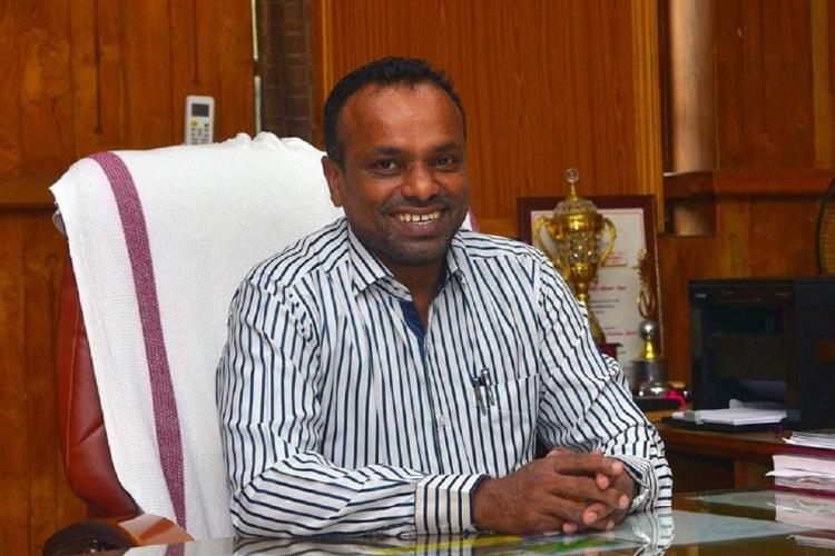 Collector Abdul Nasar sits in his office chair wearing a light coloured shirt and with a smile