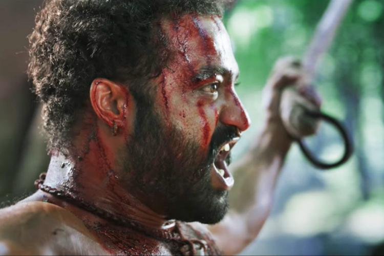 Jr NTRs bloody face as he screams while both hands are chained seen from his right