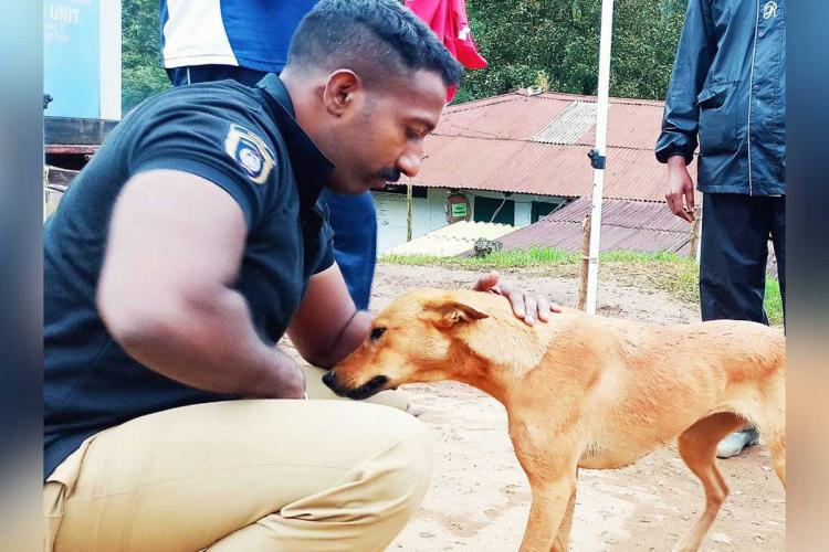 Ajith cuddling Koovi the Mongrel dog. Ajith is a trainer with the Kerala Police Dog Squad. In the image, he is seen in a pair of khaki trousers and a navy blue polo t-shirt with a insignia on his sleeve.
