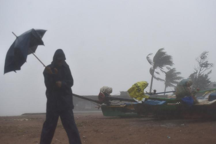 A man walking in Kovalam beach during Cyclone Nivar