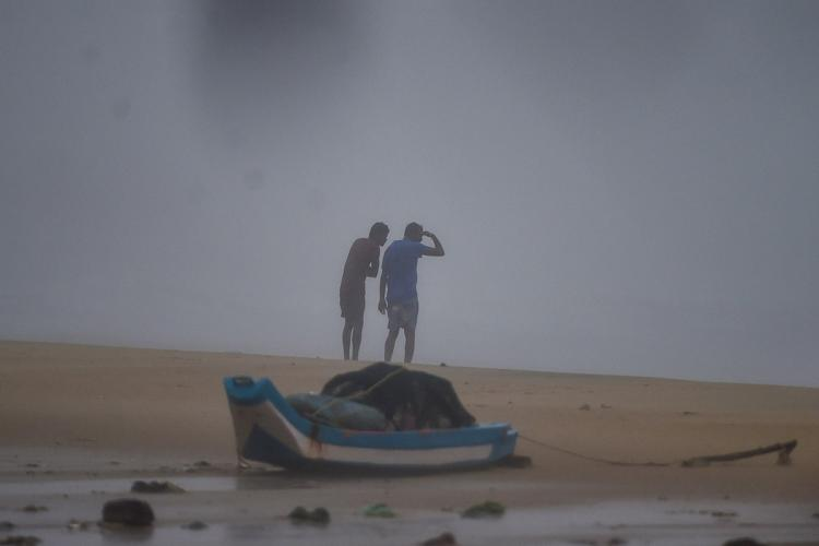 Two men at Kovalam beach during Cyclone Nivar