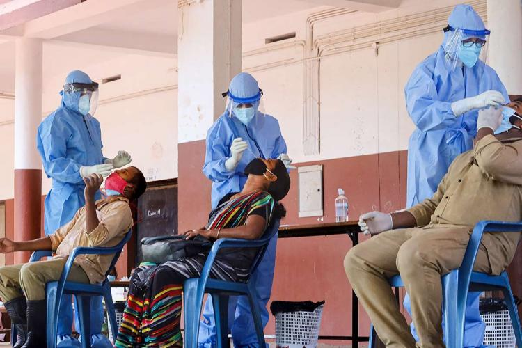 Three technicians wearing PPE take a nasal swab each from two men and one woman who are seated on chairs