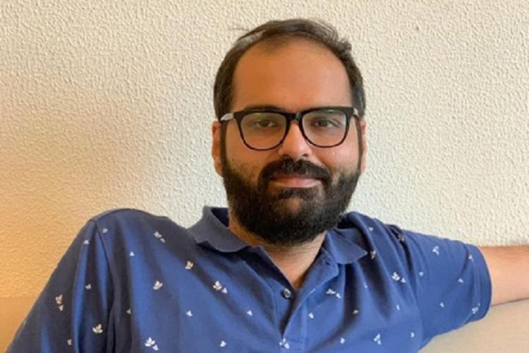 Comedian Kunal Kamra wearing a blue t-shirt and spectacles and smiling into camera