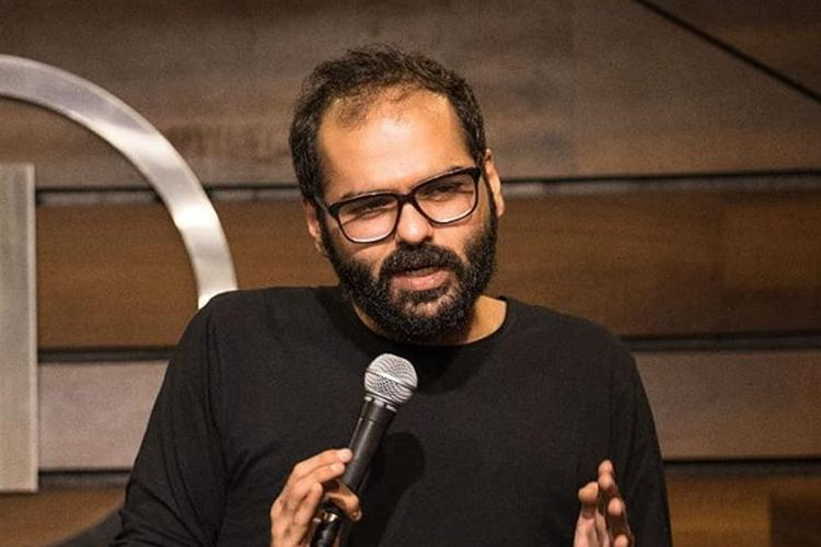 Comedian Kunal Kamra wearing a black t-shirt holding a microphone and speaking at a stand up comedy event