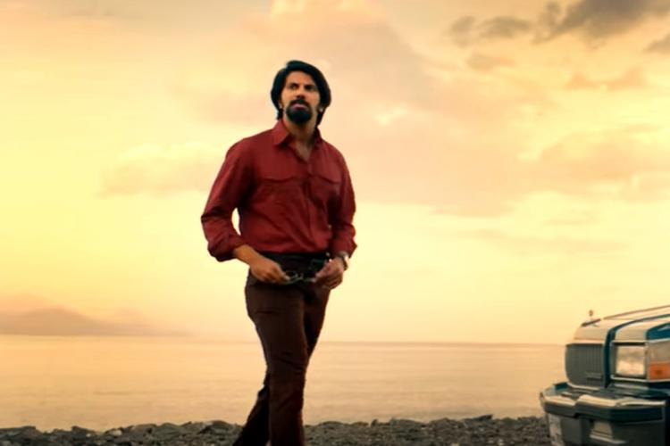 Dulquer Salmaan as Sukumara Kurup in film Kurup He is wearing a maroon shirt and brown pants