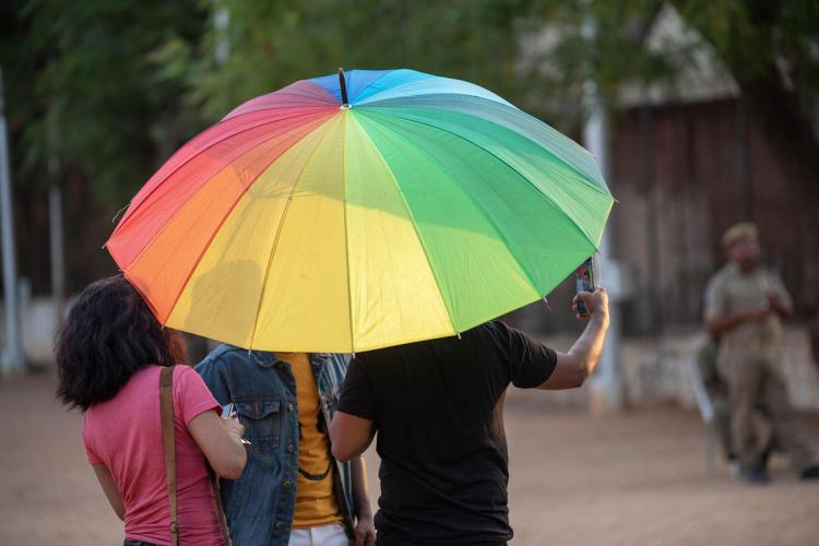 Rainbow umbrella under which three persons stand