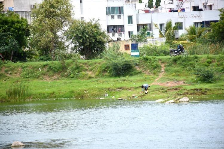 A MAN STOPS AT KILKATTALAI LAKE ON AN AFTERNOON IN CHENNAI