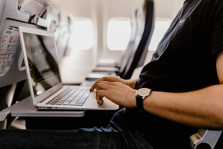 A man using a laptop on a flight
