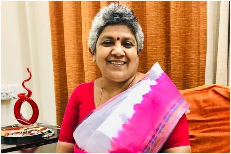 Former leader of Congress in Kerala Lathika Subhash in a pink and white saree posing for photo