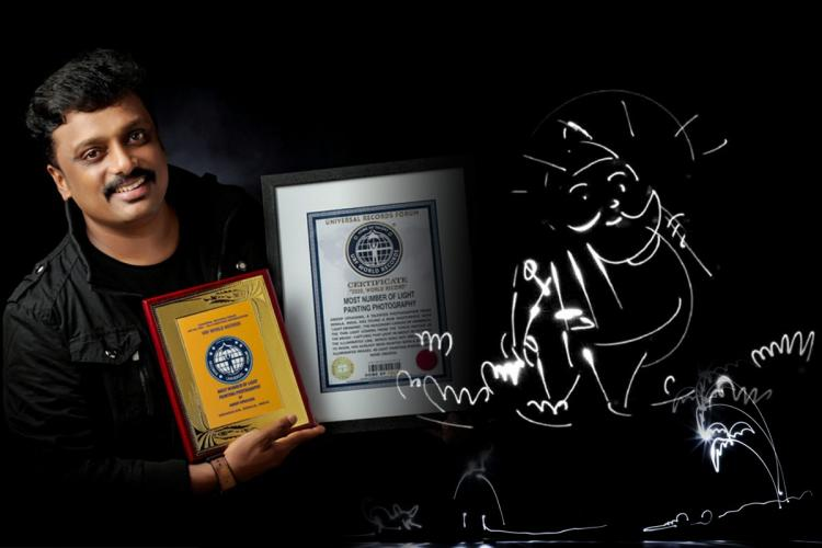 Man stands holding two certificates wearing black and in a black background with a light painting art of Mahabali on the right