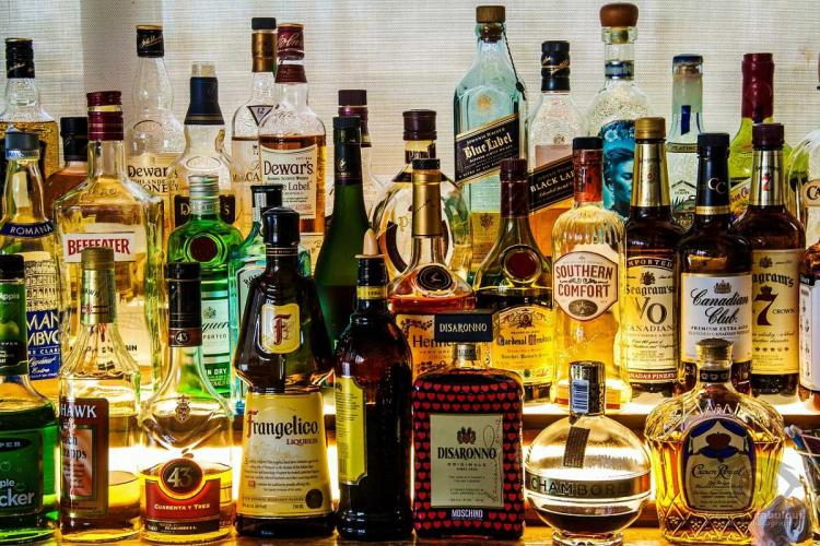 Many bottles of seemingly expensive liquor arranged together on a surface