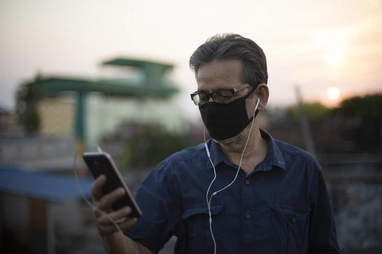 Man listening to music on phone with earphones Sun set in the background