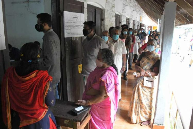 Voters in Kerala standing in queue to cast votes Women and men are in separate queues and are wearing face masks