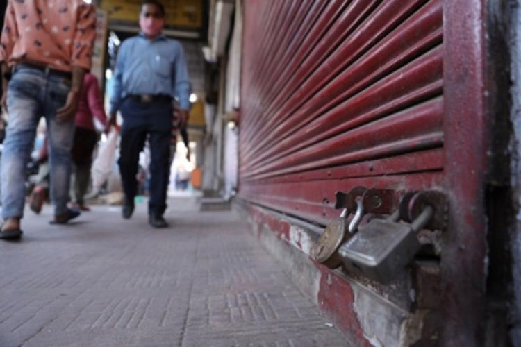 Men walk by the closed red shutter of a shop, in this close-up shot of the shutter and its lock at the bottom