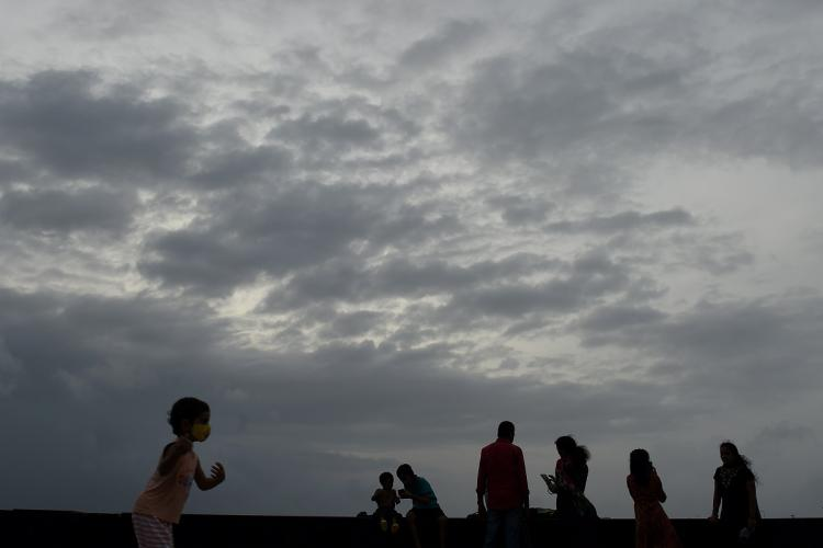 A few people including a child are outside under a cloudy grey sky