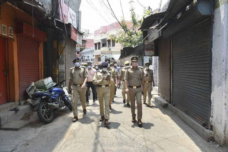 A bunch of police personnel walk through a deserted street where shutters of shops are seen closed