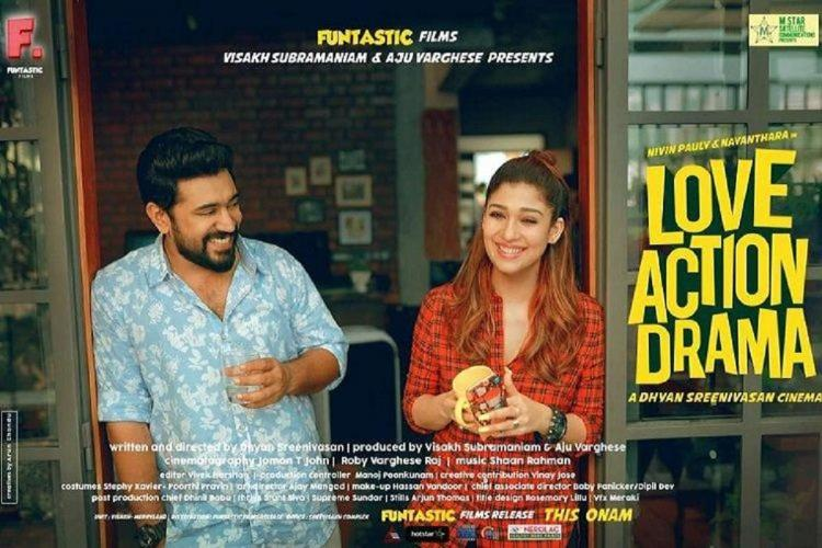 Nivin Pauly in blue shirt and Nayanthara in red stand next to each other with coffee mugs in hand and laughing