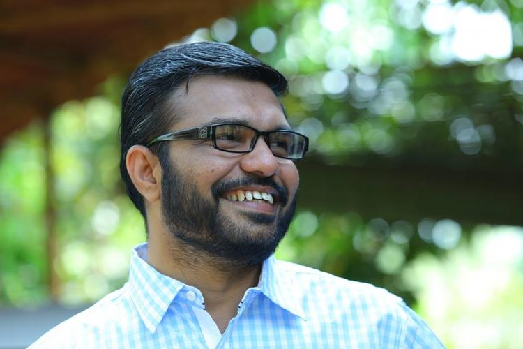 MB Rajesh smiling wearing glasses and a light blue shirt
